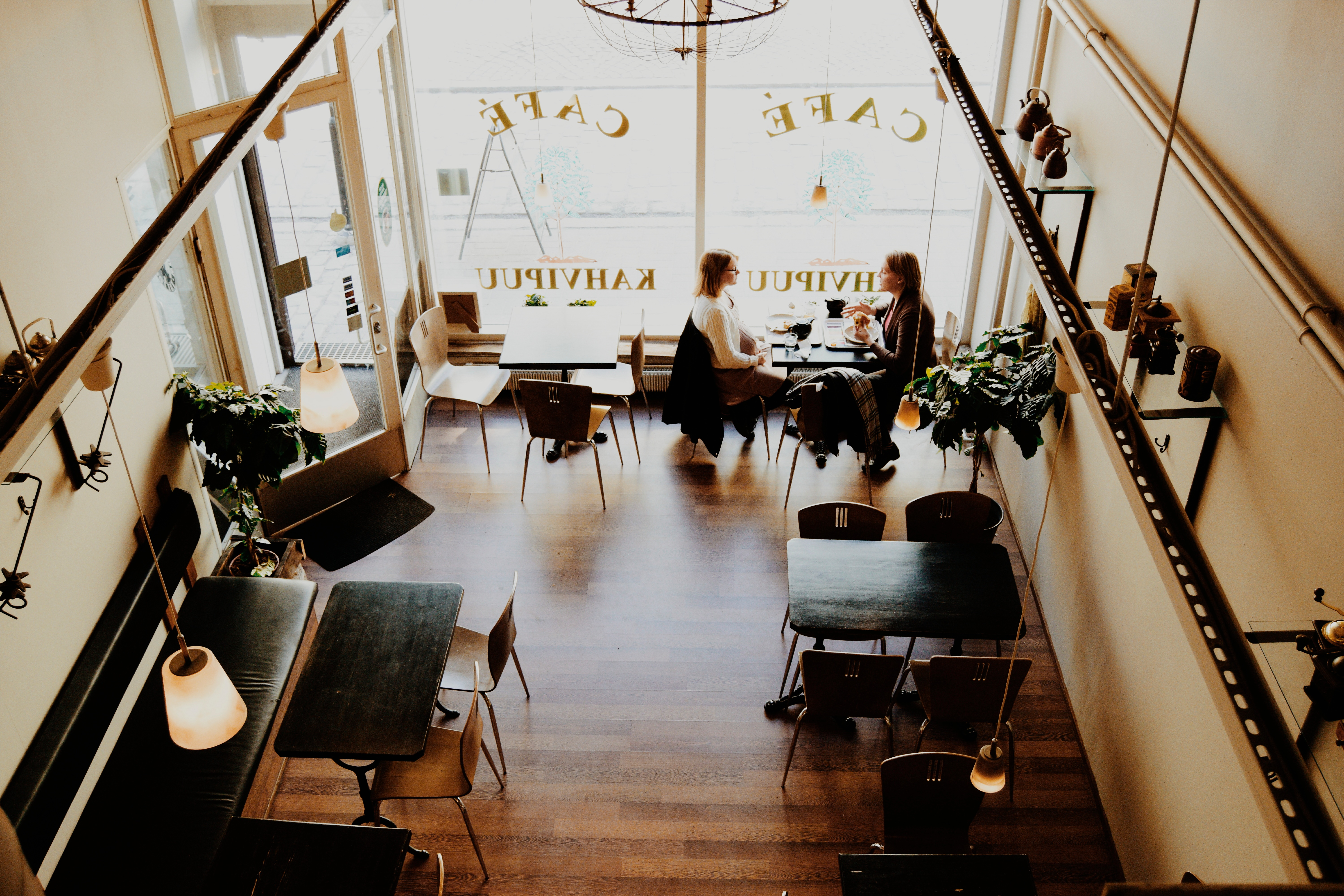 birds eye view of two women talking in a coffee cafe. They are the only ones in the room, and are sitting near the window as they talk to one another. Move Forward Counseling offers online therapy in Pennsylvania and counseling for women, so you can get support from our caring therapists from wherever you'd like!