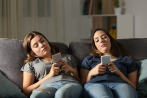 Two teenage girls slouch on the couch as they look each of their phones. Both have empty looks on their faces, and they are dealing with past trauma. Move Forward Counseling offers therapy for teens in Pennsylvania! Teen counseling in Pennsylvania is possible with online therapy in Lancaster, Erie, Allentown, Scranton, and York!